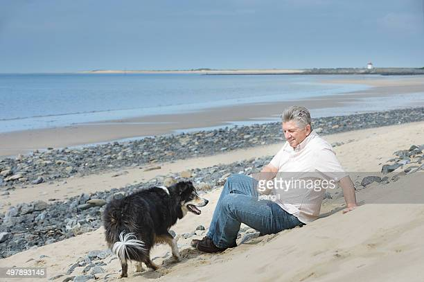 man and dog, sitting on the beach - fat guy on beach stock pictures, royalty-free photos & images