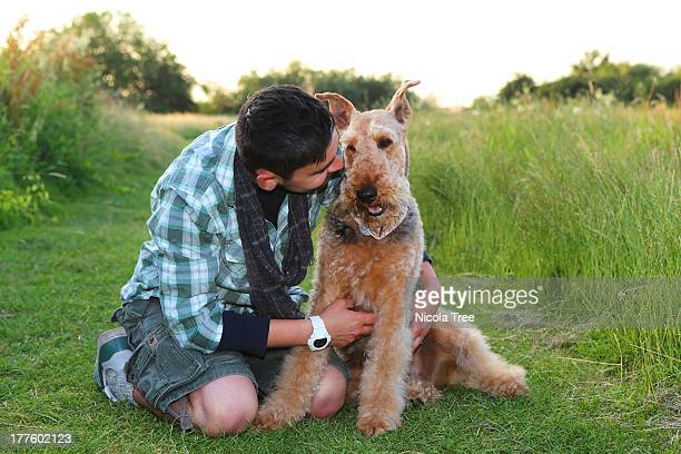 Man and dog sitting together in a landscape.