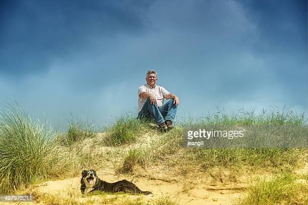 Mensch und Hund, sitzend/liegen in sand dunes
