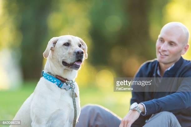 Homme et chien font une pause sur le trottoir