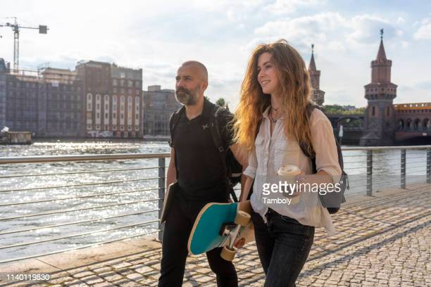 man and female friend with skateboard on bridge, river, oberbaum bridge and buildings in background, berlin, germany - friendly match stockfoto's en -beelden