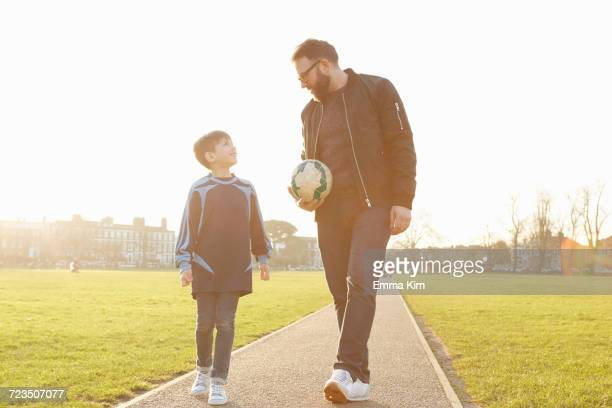 Man and football player son strolling and talking in park