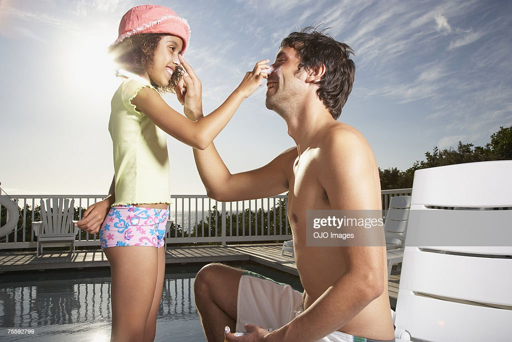 Man and girl applying sun block to noses : Stock Photo