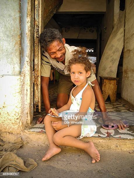 Man and girl in doorway with cookie - Trinidad, Cuba.