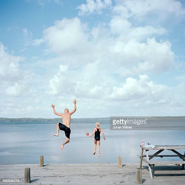 Man and girl jumping into lake
