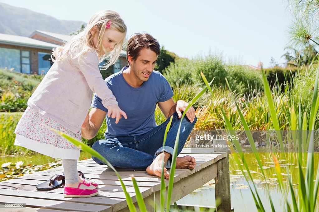 Man and girl (2-3) looking into pond from jetty : Stockfoto