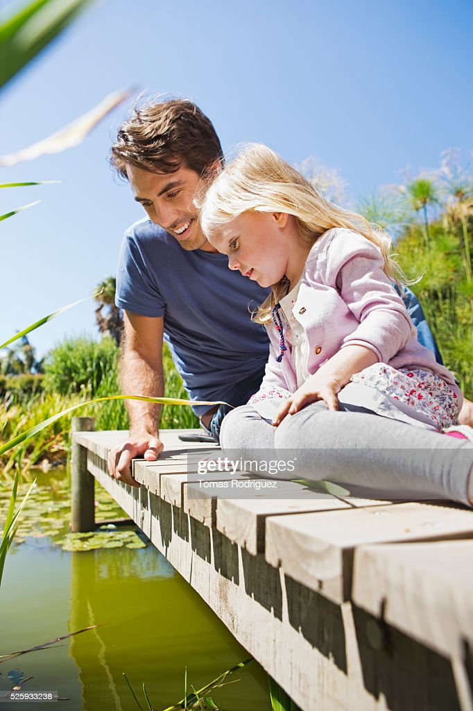 Man and girl (2-3) looking into pond from jetty : Stock Photo