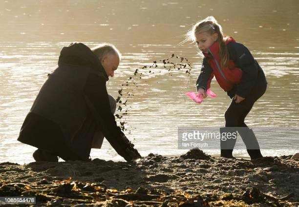 A man and girl play in the sand on the beach on New Year's Day morning on January 01 2019 in Saltburn By The Sea England