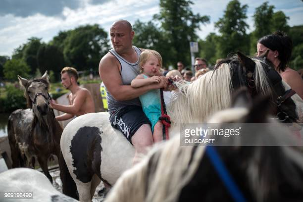 A man and girl ride a horse in the centre of ApplebyinWestmorland on the opening day of the annual Appleby Horse Fair in the town of...