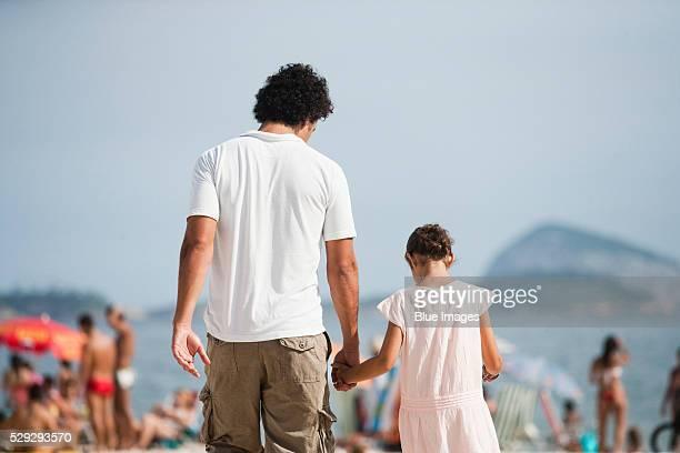 Man and girl walking on beach