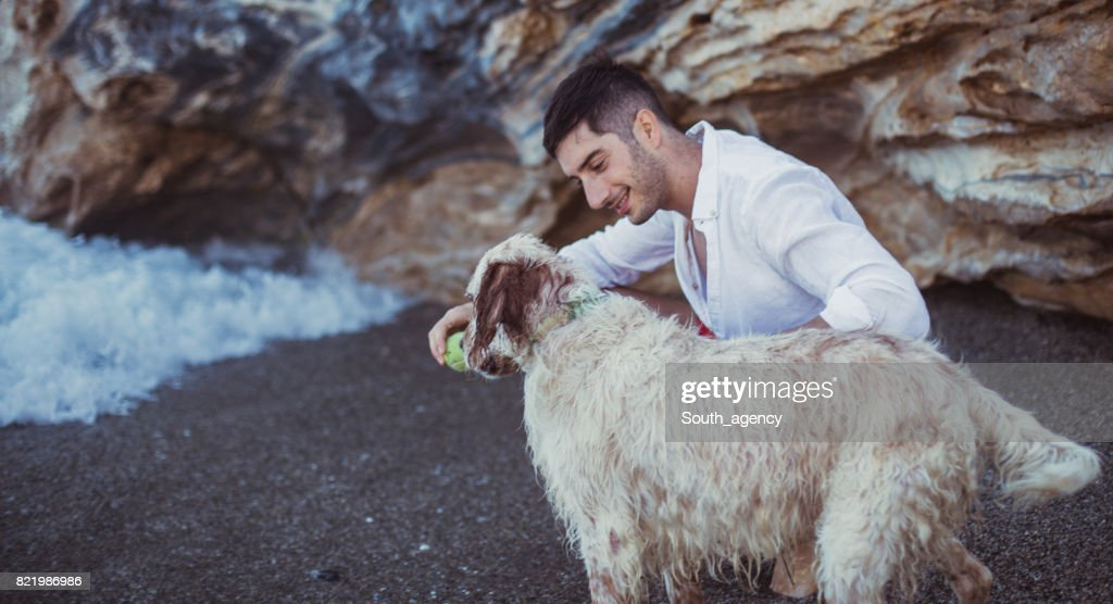 Man and his best friend at the beach : Stock Photo