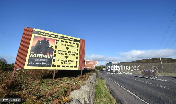 Man and his child rides their horse and cart past a fresh anti-Brexit billboard highlighting the Good Friday peace agreement as they cross the border...