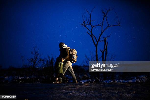 A man and his child walk through a snowcovered field after crossing the MacedonianSerbian border along with other migrants and refugees near the...