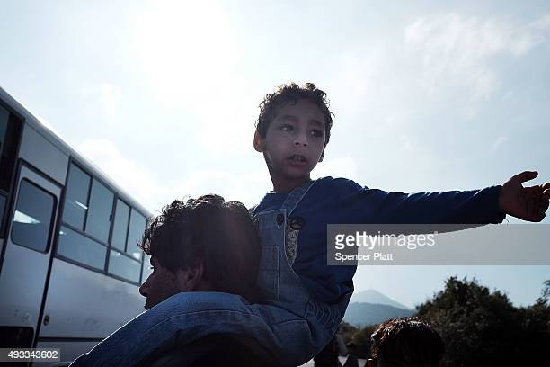 A man and his child walk with other migrants to a reception center after arriving by raft from Turkey onto the island of Lesbos on October 19 2015 in...