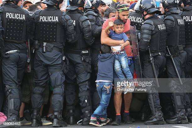 A man and his children are allowed through as migrants are held back by Slovenian riot police in the small Croatian village of Harmica on September...