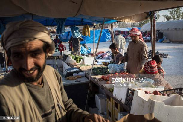 A man and his children shop for vegetables at a makeshift store at a camp for internally displaced people on October 29 2017 in Ain Issa Syria...