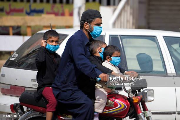 Man and his children wearing facemasks ride on a motorbike along a street during a government-imposed lockdown as a preventive measure against the...