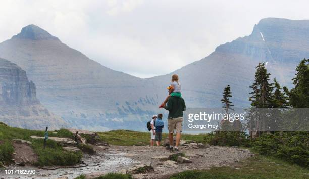 A man and his daughter and other visitors hike the Hidden Lake trail in Glacier National Park on July 26 2018 in West Glacier Montana Over crowding...