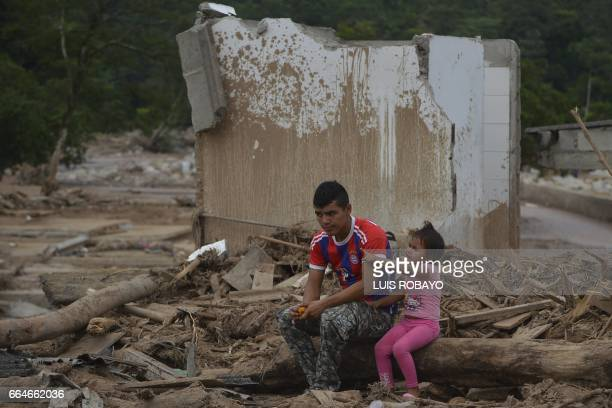A man and his daughter are in the middle of the rubble by a mudslide caused by heavy rains in Mocoa Putumayo department Colombia on April 4 2017 The...
