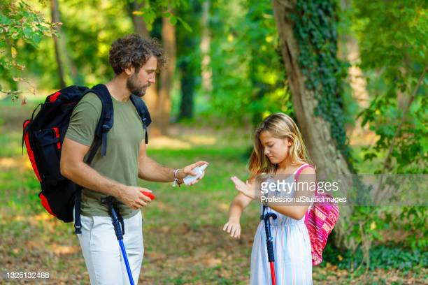man and his daughter are scratching itchy skin due to the attack of insects in nature. - insect bites images stock pictures, royalty-free photos & images