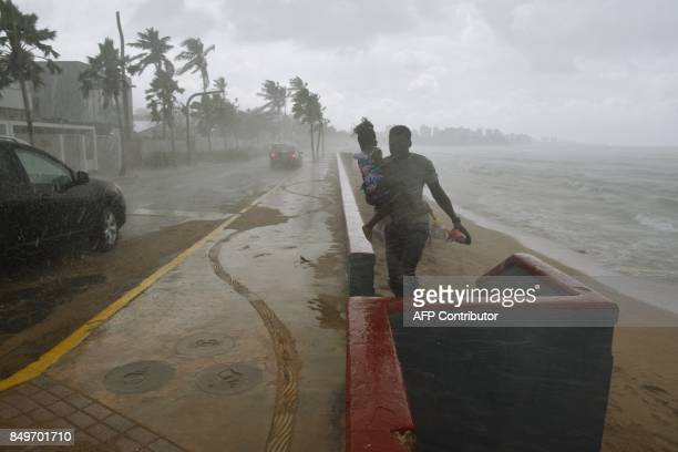 TOPSHOT A man and his daughter flee from the rain on a beach in San Juan Puerto Rico on September 19 prior to the arrival of Hurricane Maria Maria...