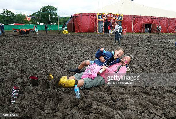 A man and his daughter get stuck in the mud on day five of the Glastonbury Festival of Music and Performing Arts on Worthy Farm near the village of...