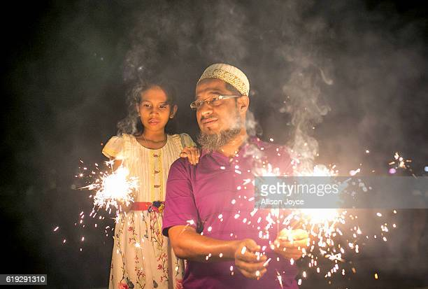 A man and his daughter hold fire cracker as Indians celebrate the annual festival of Diwali on October 30 2016 in Mumbai India Diwali the festival of...