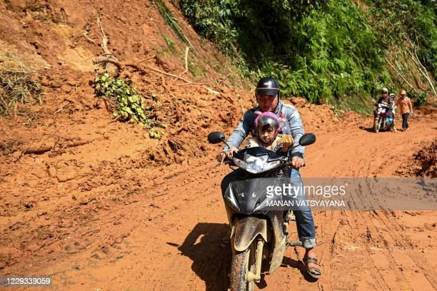 Man and his daughter ride a scooter along a road covered in mud from a landslide in central Vietnam's Quang Nam province on October 29 in the...