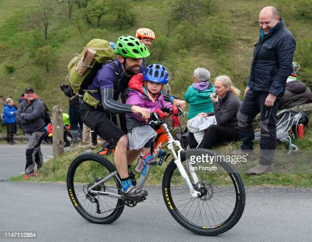 A man and his daughter ride up the Cote de Park Rash ascent near the village of Kettlewell in the Yorkshire Dales as they wait for the arrival of the...