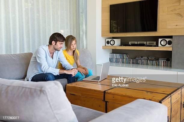 Man and his daughter sitting on a couch looking at a laptop