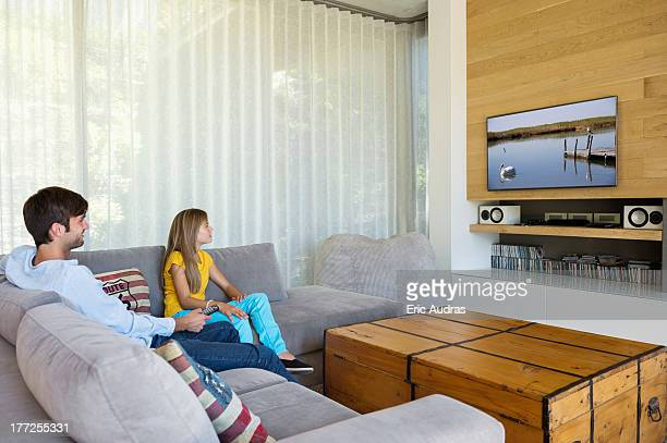 man and his daughter watching television - changing channels stock photos and pictures