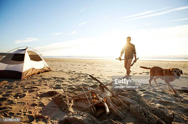 Man and his dog camping on the beach.