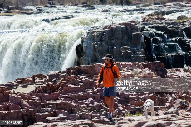 A man and his dog enjoy the outdoors at Falls Park during the coronavirus COVID19 pandemic on April 20 in Sioux Falls South Dakota For months...