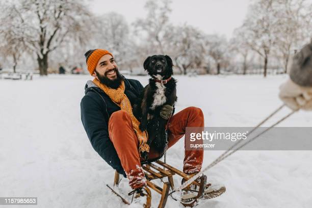 man and his dog in snow - knit hat stock pictures, royalty-free photos & images