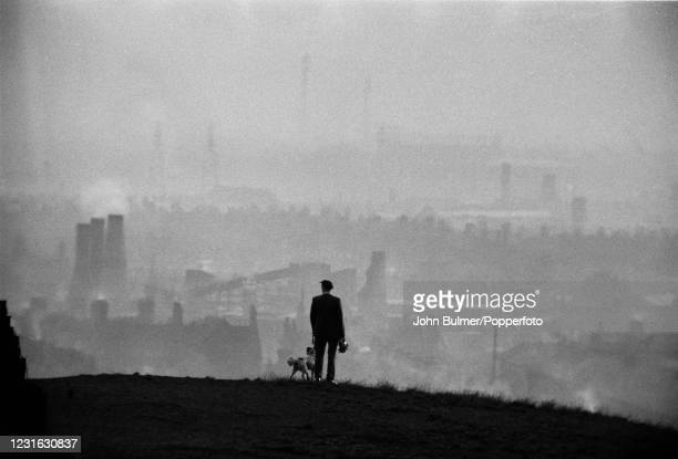 Man and his dog observing the industrial landscape from a hill overlooking the Potteries in Stoke-on-Trent, England, circa 1961.