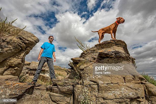 man and his dog outdoors standing on cliffs - americas next top dog stock pictures, royalty-free photos & images