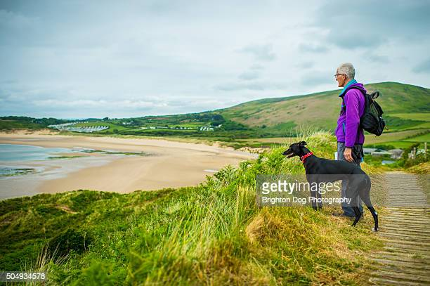 A man and his dog overlooking a beach