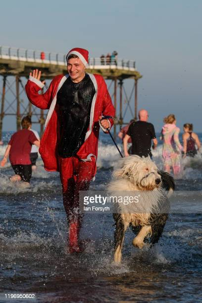 A man and his dog run through the shallows as they take part the New Year's Day Dip on January 01 2020 in Saltburn By The Sea England The event takes...