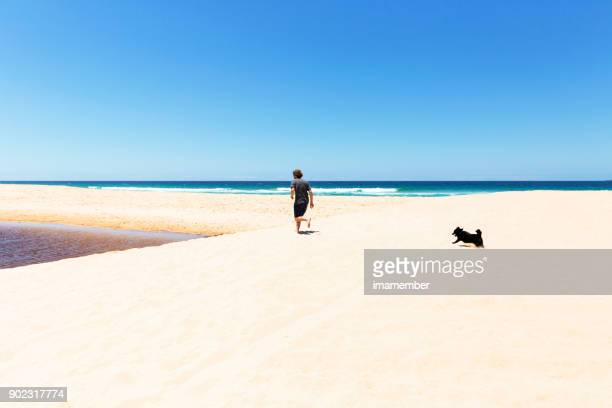 Man and his dog running on the beach, copy space