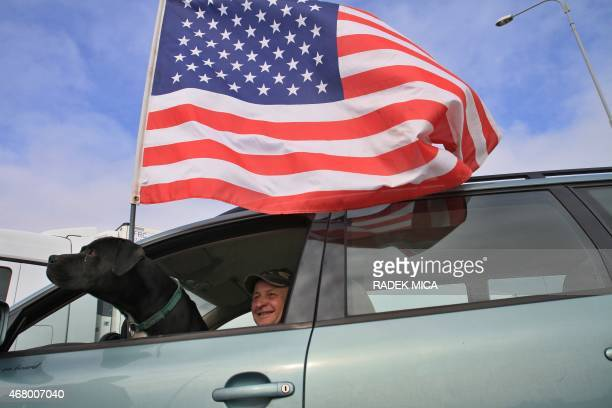 A man and his dog sit in their car with a US flag as they greet a US military convoys at Ostrava after entering the Czech Republic at the border...