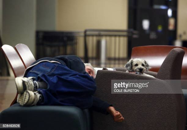A man and his dog sleep on a makeshift bed at a recreational centre in Lac la Biche Alberta on May 5 2016 after fleeing forest fires north of Fort...