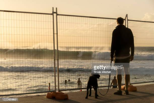 A man and his dog view the surf through a fence at Bronte Beach on May 04 2020 in Sydney Australia The beach remains closed except for exercise The...
