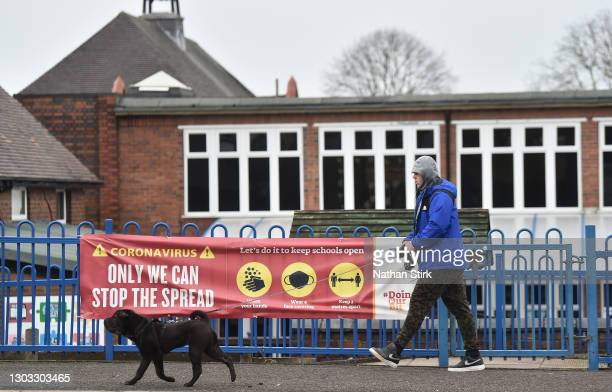 Man and his dog walk past a school's coronavirus sign, displayed onto a gate outside The Reginald Mitchell Primary School on February 21, 2021 in...