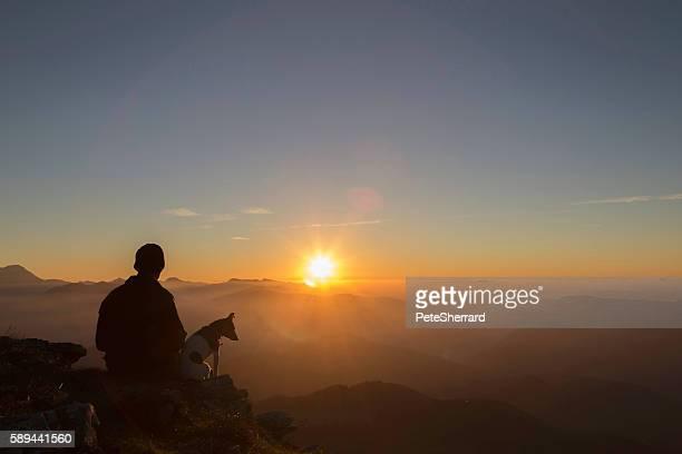 Mann und sein Hund beobachten Sie den Sonnenuntergang.