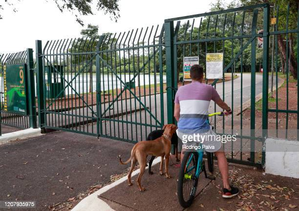 A man and his dogs by a sign that reads Park Closed' at the gates of Ibirapuera Park during a lockdown aimed at stopping the spread of the...