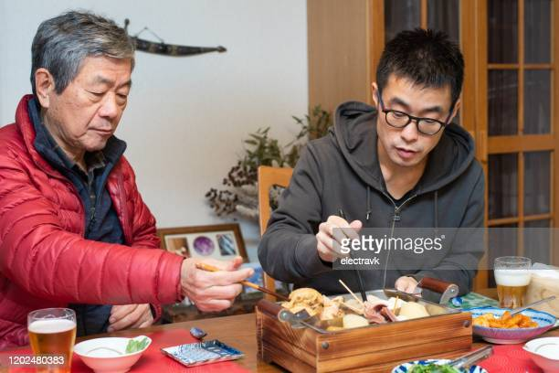 un hombre y su anciano padre preparando la cena - oden fotografías e imágenes de stock