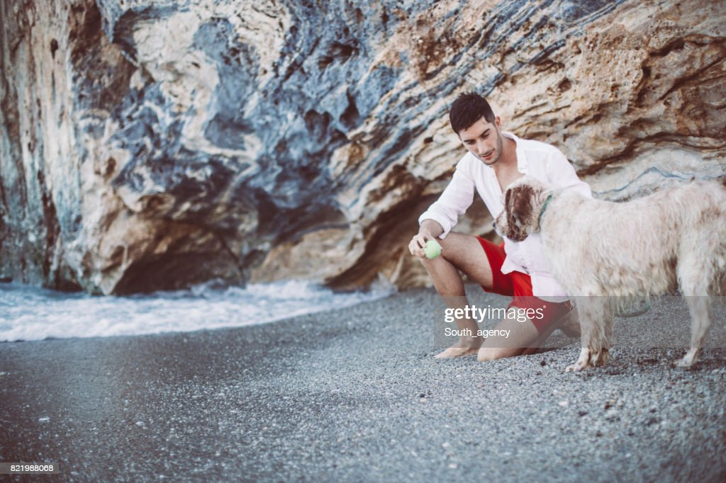 Man and his friend at the beach : Stock Photo