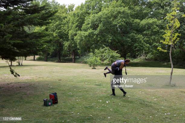 Man and his girlfriend mess about in Beckenham Palace Park in south London, on 14th June 2020, in London, England.