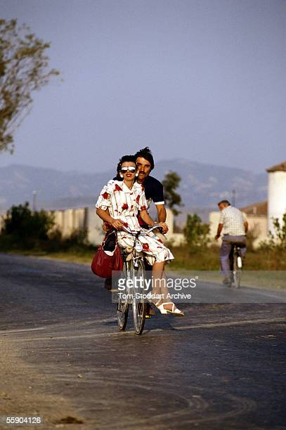 A man and his girlfriend pedal home together on a bicycle The future for young couples is brighter since the country opened up after the death of...