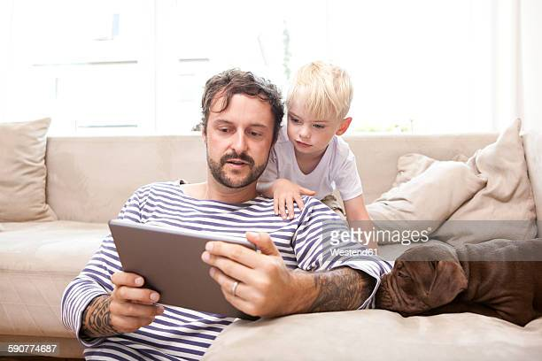 Man and his little son relaxing with digital tablet in the living room